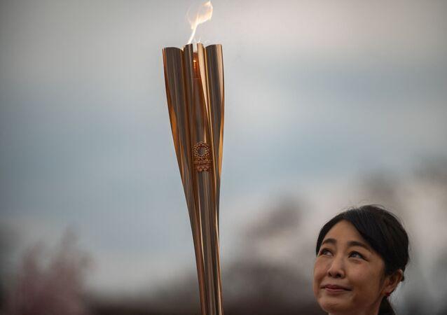 L'actrice japonaise Momoko Kikuchi regarde la torche olympique