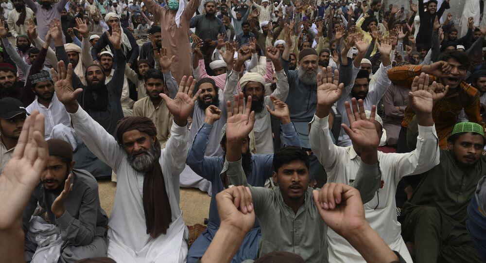 Des partisans du parti politique extrémiste Tehreek-e-Labbaik Pakistan (TLP) scandent des slogans en bloquant une rue lors d'une manifestation après l'arrestation de leur leader suite à ses appels à l'expulsion de l'ambassadeur de France, à Lahore le 16 avril 2021. (Photo par Arif ALI / AFP)