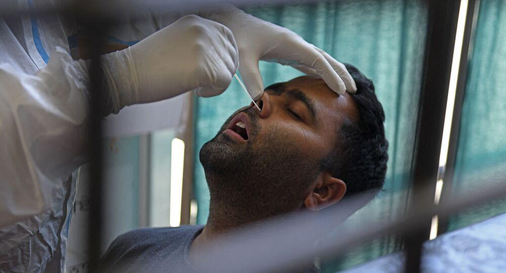 Un agent de santé prélève un échantillon par écouvillonnage nasal sur un homme pour tester le coronavirus Covid-19 à Amritsar en Inde, le 18 avril 2021.