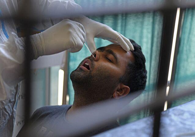 Un agent de santé prélève un échantillon par écouvillonnage nasal sur un homme pour tester le coronavirus Covid-19 à Amritsar en Inde, le 18 avril 2021. Image d'illustration