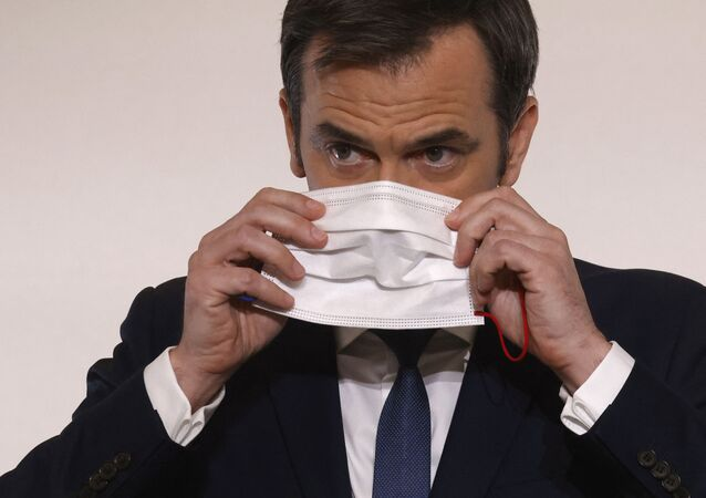 French Health Minister Olivier Veran puts on his protective face mask following a press conference on the current French government strategy for the ongoing Covid-19 pandemic in Paris, on April 22, 2021. - The peak of the third wave of the Covid-19 pandemic in France appears to be behind us, Prime Minister Jean Castex said on April 22, 2021, while travel restrictions will be relaxed from early next month. (Photo by Ludovic MARIN / POOL / AFP)