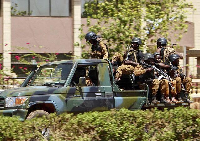 Des militaires roulent dans un véhicule près de l'ambassade de France à Ouagadougou, au Burkina Faso