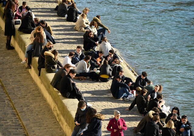 Des gens sur un quai de la Seine à Paris, le 6 mars 2021