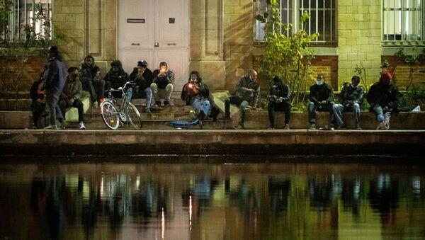 Des fumeurs de crack allument leur pipe à crack sur les quais de la place Stalingrad, surnommée Stalincrack, le 2 décembre 2020 à Paris. - Cette drogue du pauvre fait des ravages dans le nord-est de la capitale depuis trente ans. Depuis 18 mois, les autorités multiplient les initiatives pour tenter d'endiguer la consommation de ce dérivé fumable de la cocaïne : patrouilles de police renforcées, arrestations de trafiquants, hébergement des toxicomanes mais ces efforts sont pour l'instant restés largement vains. - Sputnik France