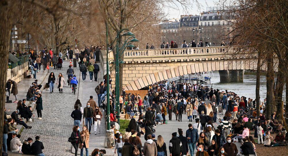 Des gens se promènent sur le quai de la Seine, à Paris, le 20 février 2021