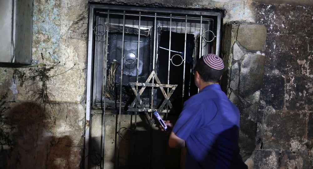 Un Israélien près d'une synagogue, après qu'elle a été incendiée par des arabo-israéliens, dans la ville de Lod le 14 mai 2021