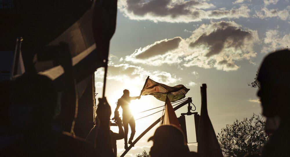 Un activiste au sommet d'un lampadaire brandit un drapeau palestinien lors d'un rassemblement, samedi 15 mai 2021, à New York. Le rassemblement soutient la Palestine dans le conflit actuel entre Israël et la Palestine, le jour où des frappes aériennes israéliennes ont rasé plusieurs bâtiments dans la bande de Gaza.