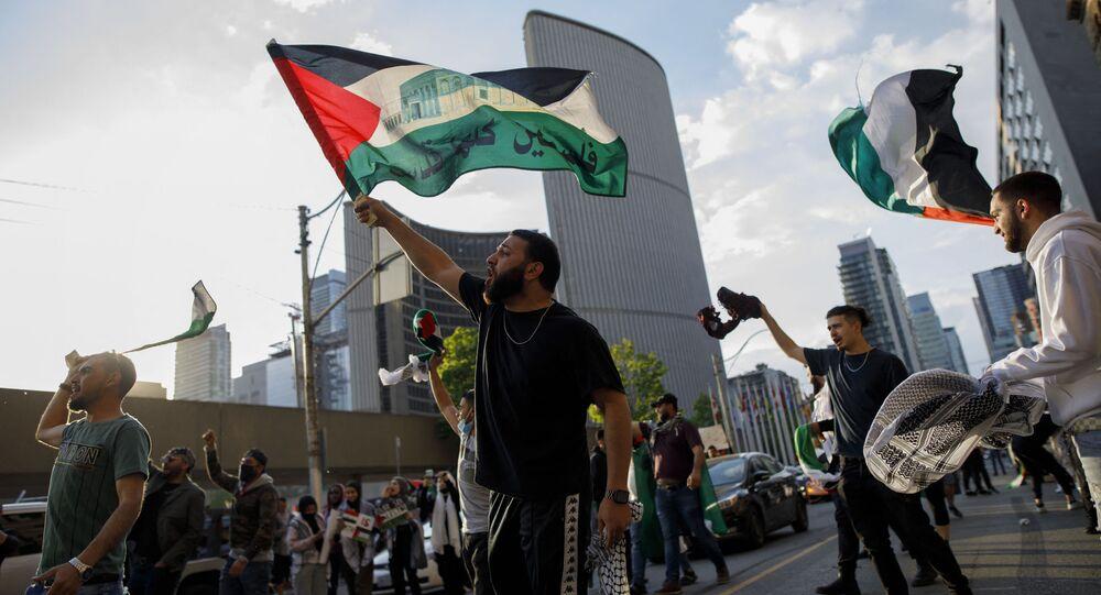 Des manifestants agitent des drapeaux pour exprimer leur soutien au peuple palestinien, à l'hôtel de ville de Toronto à Toronto, Ontario, Canada, le 15 mai 2021.