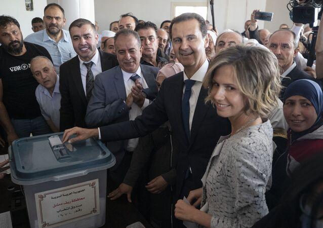 Le Président syrien Bachar el-Assad et sa femme Asma dans un bureau de vote lors de l'élection présidentielle, dans la ville de Douma, située dans la région de la Ghouta, tout proche de la capitale Damas, mercredi 26 mai, 2021