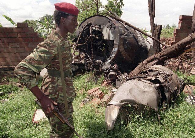 Un militaire rebelle du FPR (Front patriotique rwandais) de Paul Kagame (Tutsi) devant l'épave du Falcon 50 abattu par un tir de missile au-dessus de l'aéroport de Kigali, capitale du Rwanda, le 6 avril 1994. L'avion transportait le Président de la République rwandaise alors en exercice, Juvénal Habyarimana (Hutu), ainsi que son homologue du Burundi, Cyprien Ntaryamira.