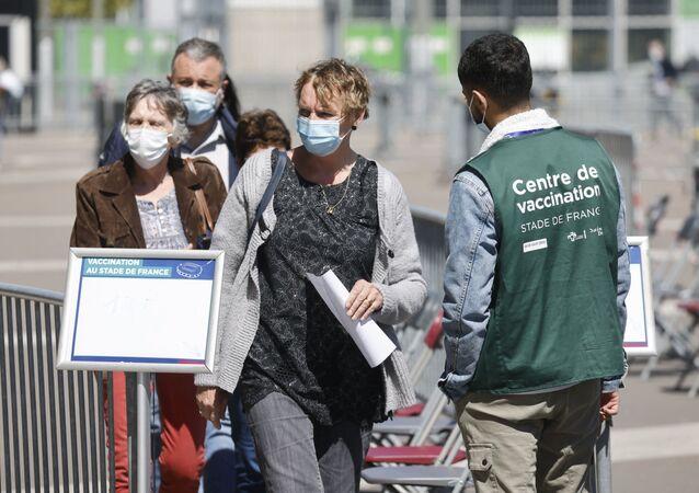 Des gens attendent devant le Stade de France à Saint-Denis pour se faire vacciner