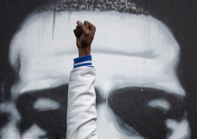 Un Afro-Américain lève sa main devant l'image de George Floyd à Minneapolis, États-Unis, avril 2021