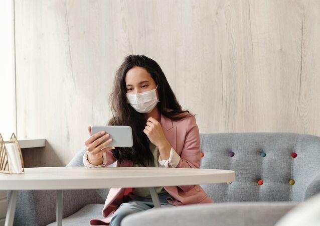 Une femme en masque de protection avec un smartphone (image d'illustration)