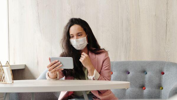 Une femme en masque de protection avec un smartphone (image d'illustration) - Sputnik France