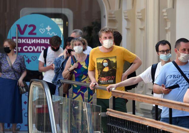 Des gens devant un centre de vaccination ouvert dans le grand magasin Goum, sur la place Rouge