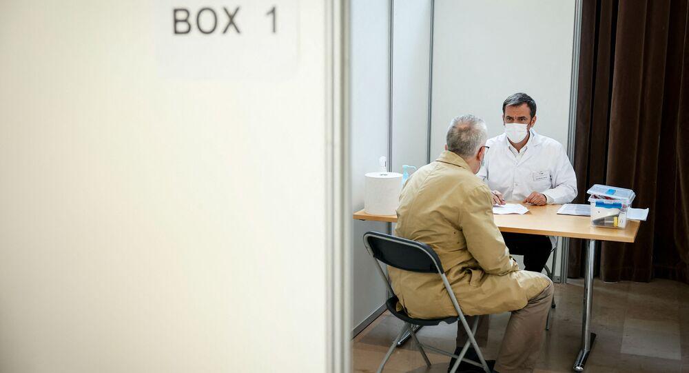 Le ministre de la Santé et des Solidarités Olivier Véran reçoit un patient au centre de vaccination de Montrouge, mai 2021