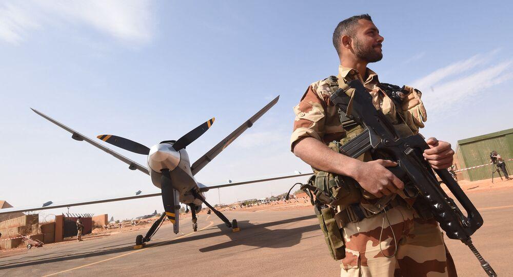 Soldat de l'opération Barkhane, devant un drone Reaper à l'aéroport militaire nigérian de Diori Hamani, le 2 Janvier 2015. AFP PHOTO / DOMINIQUE FAGET (Photo by DOMINIQUE FAGET / AFP)