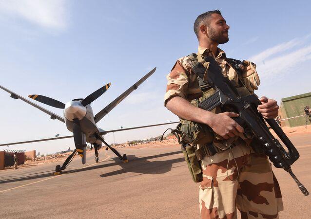 Soldat de l'opération Barkhane, devant un drone Reaper à l'aéroport militaire nigérian de Diori Hamani