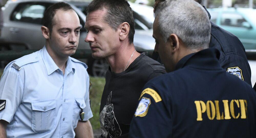 Alexandre Vinnik (au centre) escorté par des agents de police grecs (archive photo)