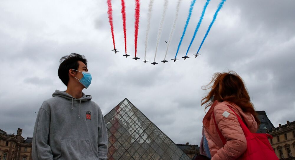 Des spectateurs portant des masques regardent le survol des avions à l'occasion de la Fête nationale française, le 14 juillet 2021