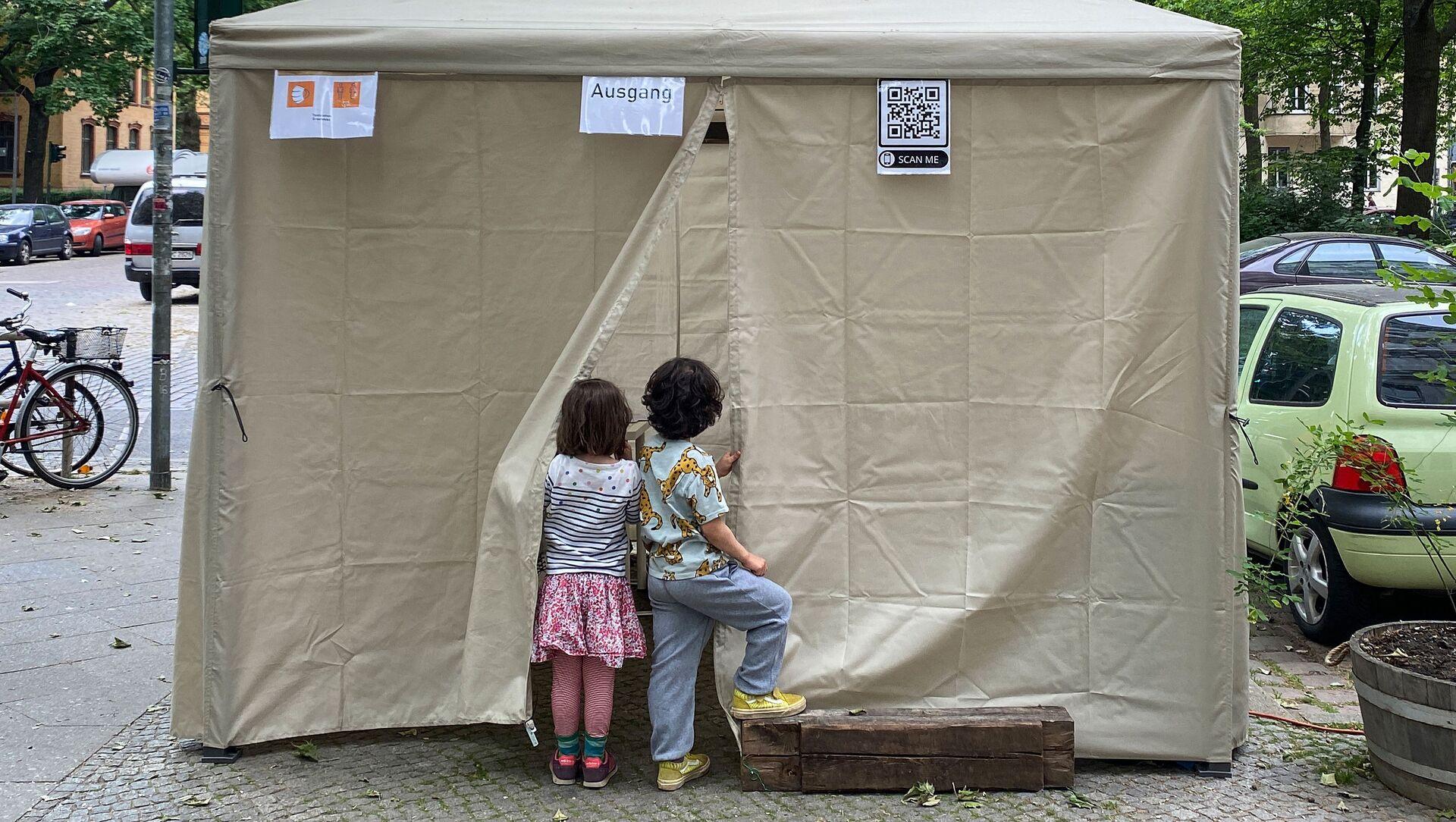 Deux enfants attendent leurs parents devant un lieu de dépistage du Covid-19, à Berlin en Allemagne - Sputnik France, 1920, 26.07.2021