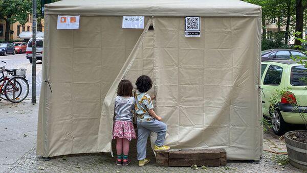 Deux enfants attendent leurs parents devant un lieu de dépistage du Covid-19, à Berlin en Allemagne - Sputnik France