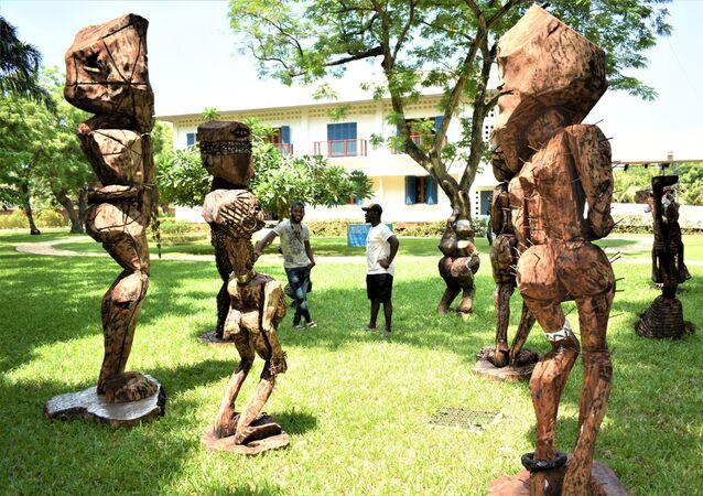 Devant les sculptures sous le titre de l'humanité, l'Atisso Goha échange avec un autre visiteur