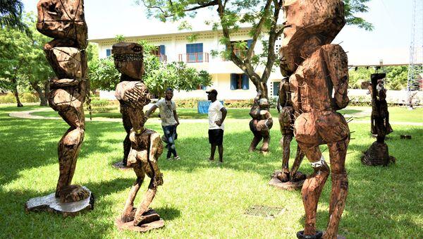 Devant les sculptures sous le titre de l'humanité, l'Atisso Goha échange avec un autre visiteur - Sputnik France
