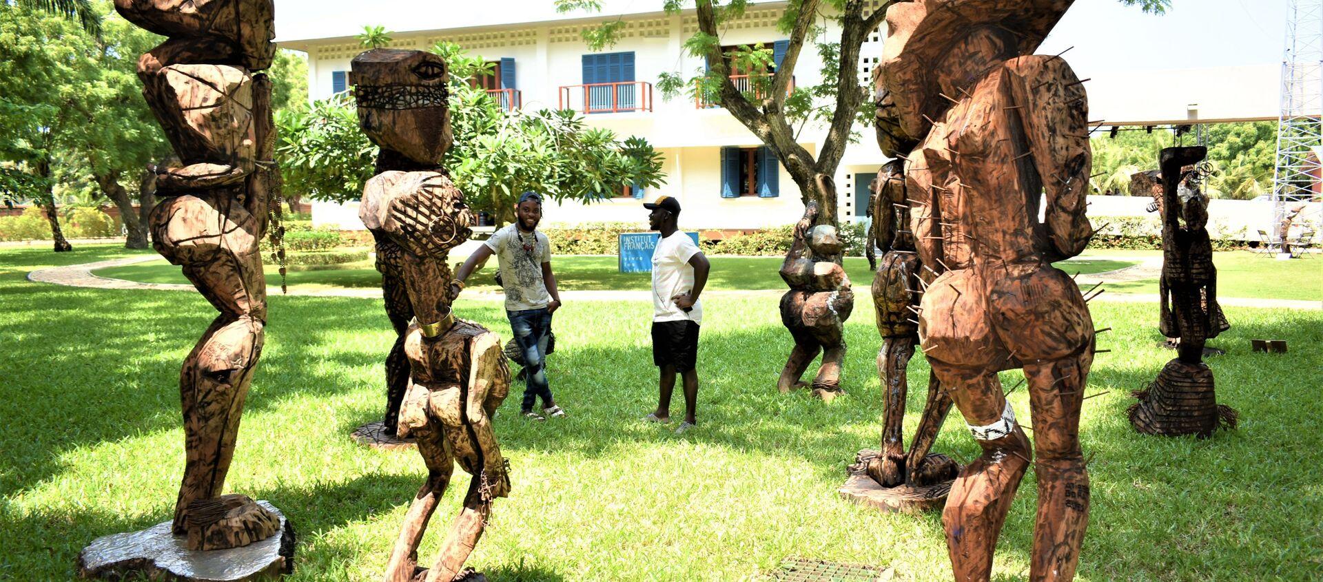 Devant les sculptures sous le titre de l'humanité, l'Atisso Goha échange avec un autre visiteur - Sputnik France, 1920, 30.07.2021