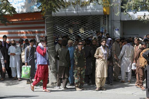 Paniqués, les habitants de Kaboul fuient la ville. Il y a une véritable frénésie dans les banques: beaucoup se sont précipités pour fermer leurs comptes avant de s'enfuir.Sur la photo: une file d'attente devant une banque à Kaboul. - Sputnik France