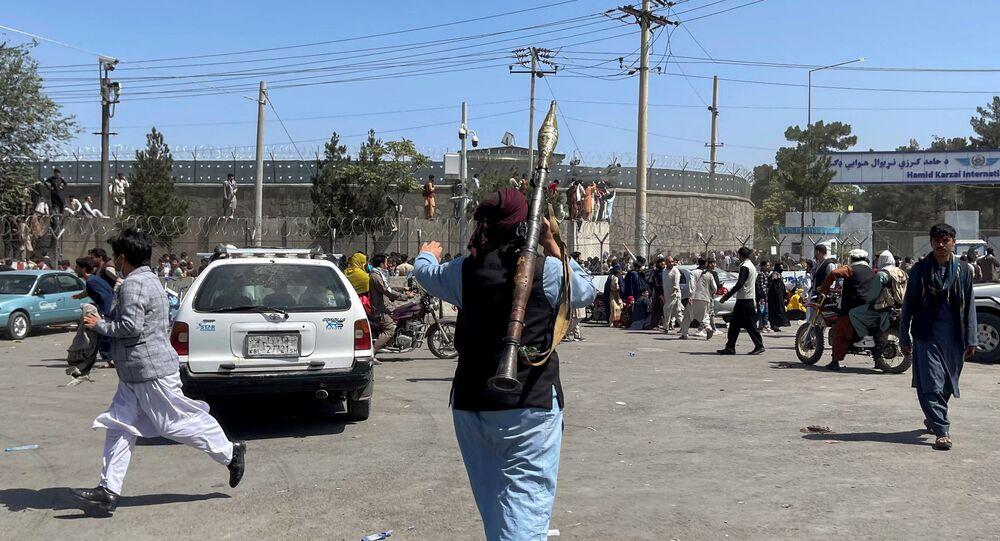Un combattant du mouvement taliban patrouille la zone à l'intérieur de l'aéroport de Kaboul, le 16 août 2021