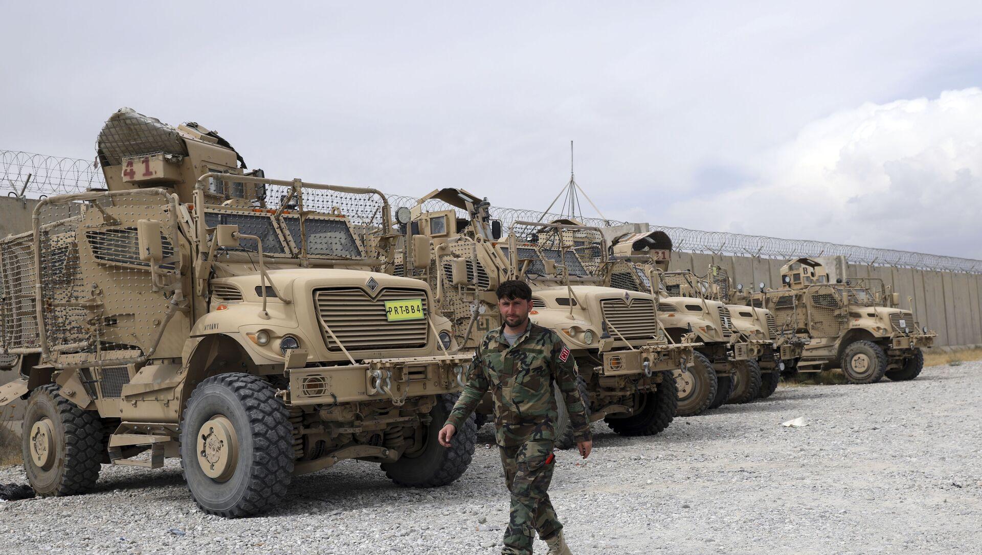 Un soldat de l'armée afghane passe devant des véhicules MRAP (Mine Resistant Ambush Protected) laissés sur place après le départ de l'armée américaine de la base aérienne de Bagram, dans la province de Parwan, au nord de Kaboul, en Afghanistan, lundi 5 juillet 2021. Les États-Unis ont quitté l'aérodrome de Bagram en Afghanistan après presque 20 ans, mettant fin à leur guerre éternelle, dans la nuit, sans avertir le nouveau commandant afghan plus de deux heures après leur départ.  - Sputnik France, 1920, 25.08.2021