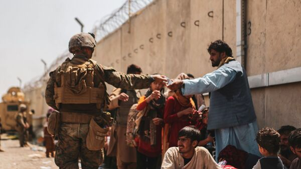 A US Marine passes out water to evacuees during an evacuation at Hamid Karzai International Airport, Kabul, Afghanistan, August 22, 2021 - Sputnik France