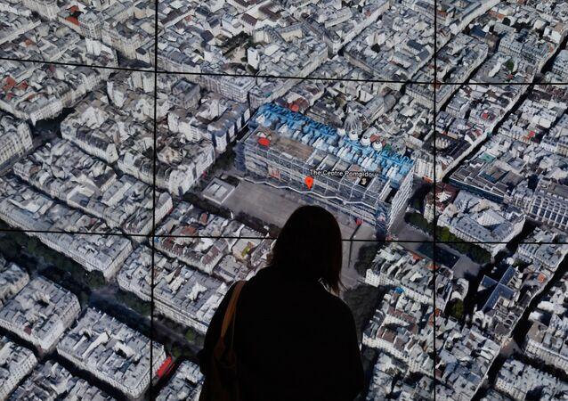 Une personne observe la carte de Paris de Google Earth. (Photo by TIMOTHY A. CLARY / AFP)