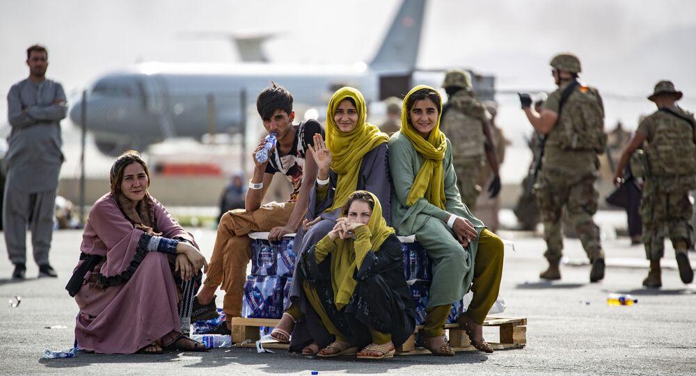 Des femmes et enfants attendent leur vol à l'aéroport de Kaboul