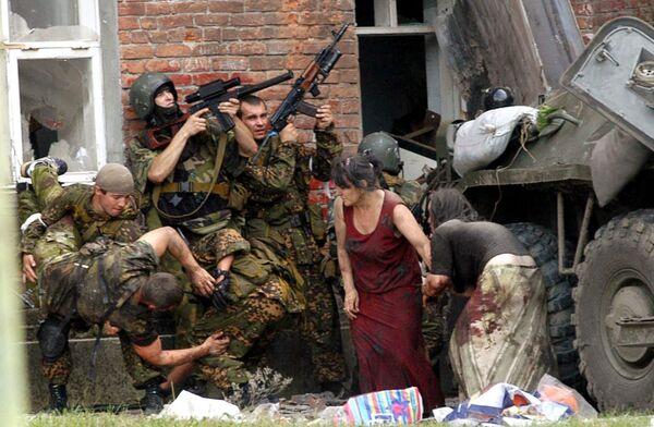 Après avoir conduit les otages dans le bâtiment, les terroristes ont commencé à installer des engins explosifs improvisés remplis de vis et de clous. Ils les ont suspendus au plafond, disposés sur des chaises et par terre, à côté des enfants. Par mesure d'intimidation, plusieurs otages ont été abattus sous les yeux de tout le monde. Sur la photo: opération de sauvetage des otages à Beslan, le 3 septembre 2004. - Sputnik France