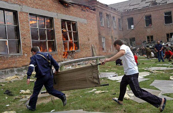 Beaucoup ne pouvaient vraiment plus le supporter. Des petits enfants sont morts dans les bras de leurs parents. La dernière chose qu'ils ont vue était les engins explosifs suspendus au-dessus de leur tête. Sur la photo: opération de sauvetage des otages à Beslan, le 3 septembre 2004. - Sputnik France