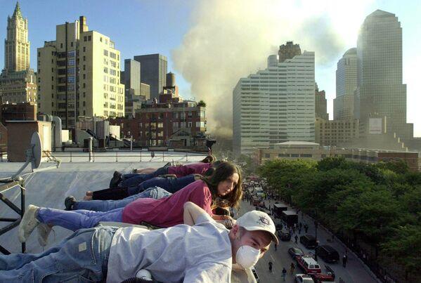 Le vol UA 175 d'United Airlines a percuté la tour sud WTC2 au niveau des étages 78-85 vers 9h03. Sur la photo: des gens regardent l'opération de sauvetage après l'attaque terroriste du 11 septembre depuis le toit d'un immeuble rue Greenwich Street à New York.  - Sputnik France