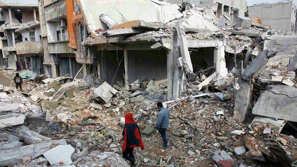 Les gens marchent sur les débris de bâtiments endommagés par l'EI en janvier de la ville syrien du Nord de Kobani - Sputnik France