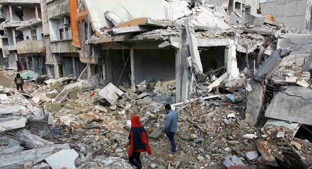 Les gens marchent sur les débris de bâtiments endommagés par l'EI en janvier de la ville syrien du Nord de Kobani