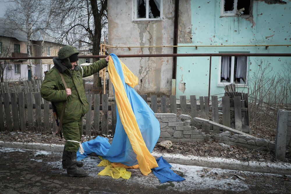 Un insurgé de la république populaire autoproclamée de Donetsk s'empare d'un drapeau ukrainien