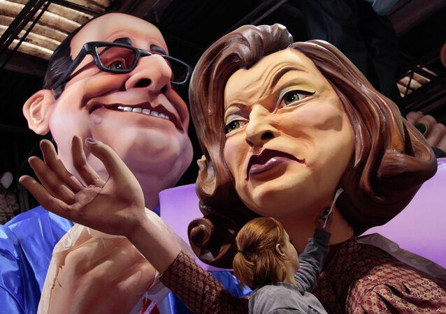 Un ouvrier met la touche finale sur les figures géantes de président français Francois Hollande (L) et son ancienne compagne Valerie Trierweiler
