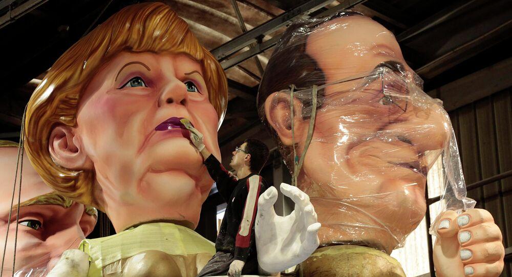 Un ouvrier met la touche finale sur les figures géantes de chancelier allemand Angela Merkel (L) et de président français Francois Hollande