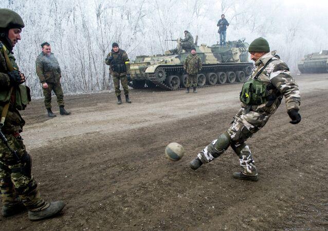 Les militaires ukrainiens jouent le football sur la route à Svitlodarsk, région de Debaltsevo le 15 février 2015
