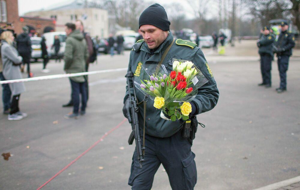 Un policier apporte des fleurs vers le centre culturel de Krudttønden à Copenhague