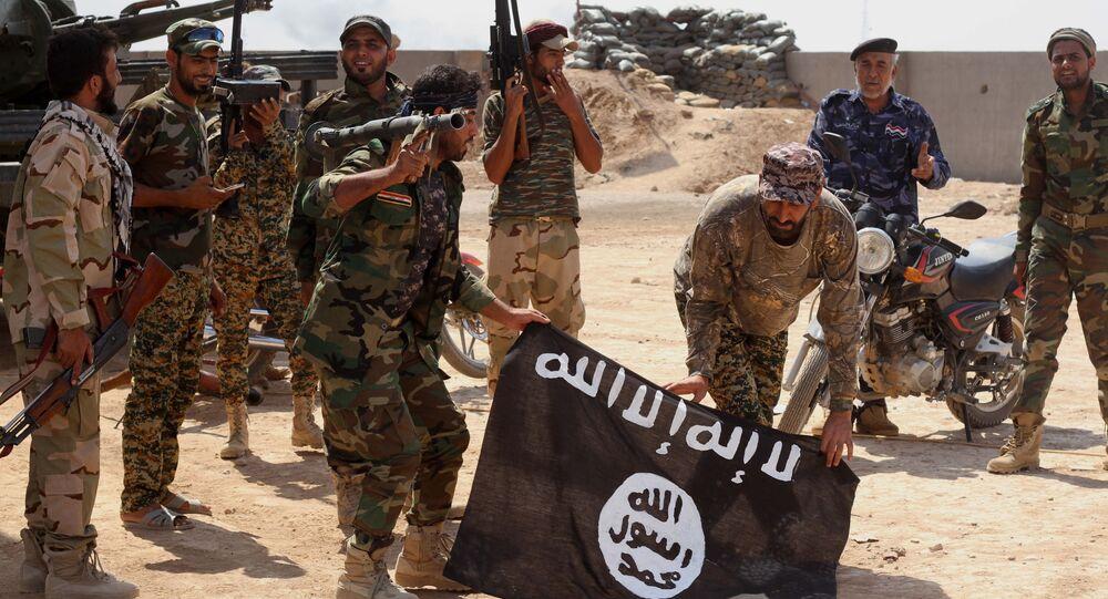 Des militaires des forces de sécurité irakiennes tiennent le drapeau de l'EI après une opération antiterroriste