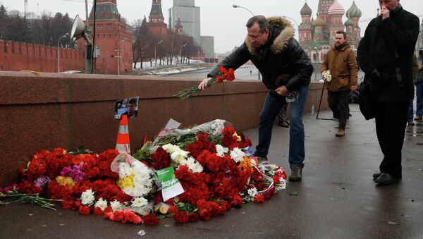 People come to lay flowers at the site, where Boris Nemtsov was shot dead, with St. Basil's Cathedral (R) and the Kremlin walls seen in the background, in central Moscow, February 28, 2015. - Sputnik France