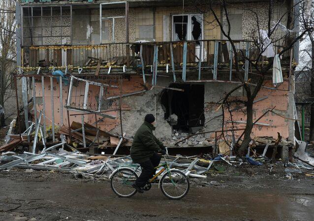 Le citadin Debaltsevo va à bicyclette devant la maison détruite à la suite des bombardements pendant les hostilités. 01.03.2014