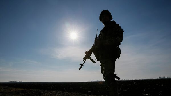 A member of the Ukrainian armed forces is silhouetted as he stands at his position near Kramatorsk, March 11, 2015 - Sputnik France