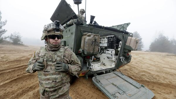 Soldiers of the U.S. Army's 2nd Cavalry Regiment, deployed in Latvia as part of NATO's Operation Atlantic Resolve, are pictured near their armored vehicle named Stryker during a joint military exercise in Adazi, Latvia - Sputnik France